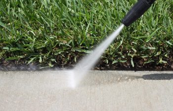 pressure cleaning being done to a sidewalk