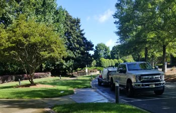 Alpharetta Pressure Washing truck with cleaning equipment parked on a driveway in a residential area