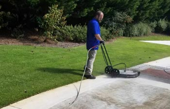 Alpharetta Pressure Washing worker cleaning concrete paver