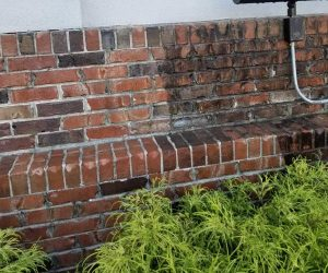 red-brick wall before and after pressure washing
