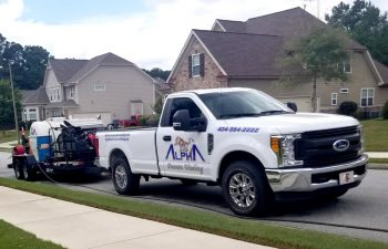 Alpharetta Pressure Washing truck with wquipment parked in front of a residential house