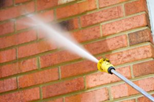 brick wall undergoing pressure washing