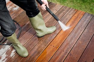 Person Pressure Washing a Wooden Deck Alpharetta GA